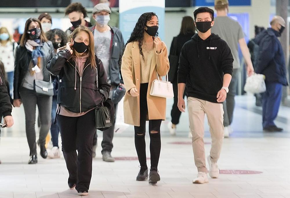 La gente usa máscaras faciales mientras camina por un centro comercial en Montreal,
