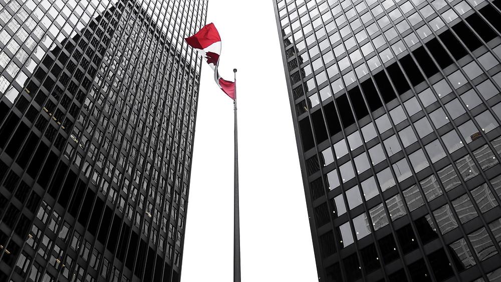 La bandera canadiense ondea al viento en el distrito financiero del centro de Toronto.