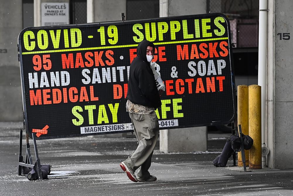 Un hombre pasa junto a un letrero de suministros minoristas de COVID-19 durante la pandemia de COVID-19 en Toronto el viernes 5 de febrero de 2021.