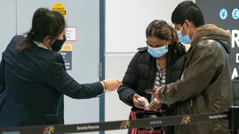 Dos viajeros en el Aeropuerto Internacional Pearson el 23 de febrero. Los pasajeros aéreos que aterricen en Canadá y se nieguen a la cuarentena en un hotel podrían enfrentar una multa de $ 5.000 a partir del viernes.
