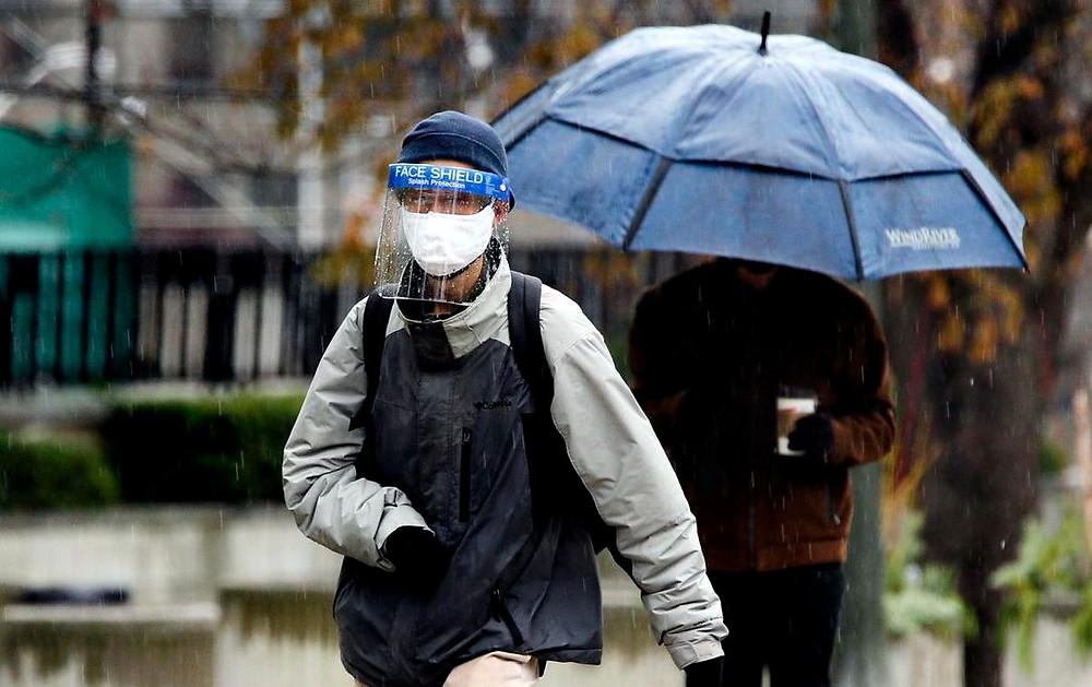 Un hombre que lleva un protector facial camina bajo la lluvia en Queen's Park Cres. E., en Toronto el 30 de noviembre.