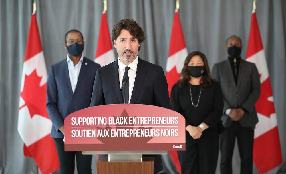 El primer ministro Justin Trudeau anunció un programa el miércoles que entregará hasta 221 millones de dólares en fondos públicos y privados para empresas y empresarios de propiedad negra. Detrás de él están Mary Ng, ministra de Pequeñas Empresas, Promoción de Exportaciones y Comercio Internacional, y el parlamentario Greg Fergus, jefe de la bancada negra liberal y a la derecha está Ahmed Ismail, cofundador de Hxouse. Trudeau hizo el anuncio en Hxouse, un centro de pensamiento enfocado globalmente con sede en Toronto.