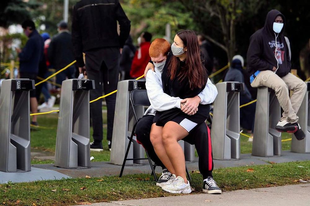 Una pareja comparte una silla mientras espera una evaluación de COVID-19 afuera del Hospital Michael Garron en Toronto