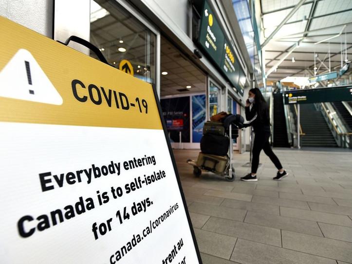 Un viajero pasa junto a la señalización en el Aeropuerto Internacional de Vancouver (YVR).
