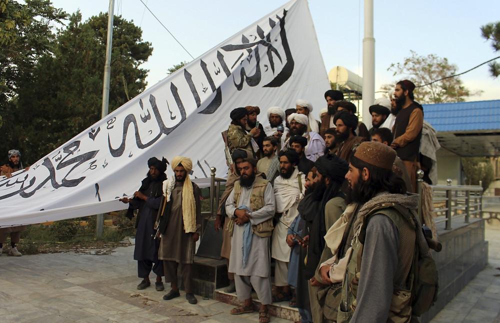 Los combatientes talibanes izan su bandera en la casa del gobernador provincial de Ghazni, en Ghazni, sureste de Afganistán, el domingo 15 de agosto de 2021.