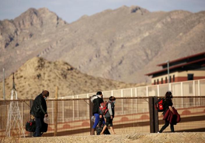 Migrantes caminan después de cruzar el río Bravo para entregarse para solicitar asilo en El Paso, Texas, Estados Unidos, visto desde Ciudad Juárez, México, el 1 de febrero de 2021.