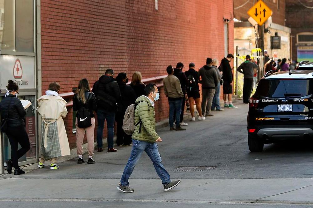 Un hombre pasa junto a una gran fila de personas que esperan una evaluación de COVID-19 en Dundas St. E. en Toronto, el 21 de septiembre de 2020