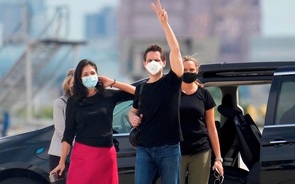 Michael Kovrig, centro derecha, saluda a los medios como su esposa Vina Nadjibulla, centro izquierda, y su hermana Ariana Botha después de su llegada al Aeropuerto Internacional Pearson en Toronto, el sábado 25 de septiembre de 2021.