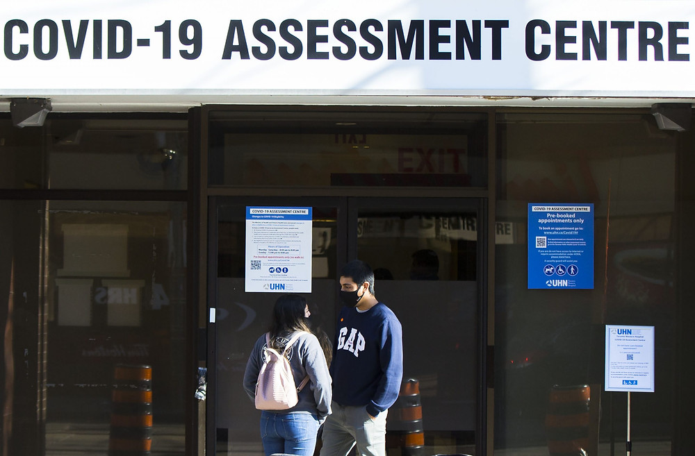 Las personas con máscaras faciales esperan las pruebas de COVID-19 fuera de un centro de evaluación de COVID-19 en Toronto,