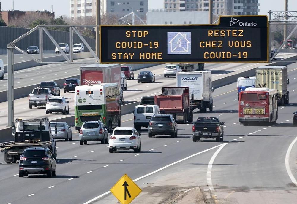 El tráfico en la autopista 401 en Toronto pasa bajo un letrero COVID-19 el lunes 6 de abril de 2020.
