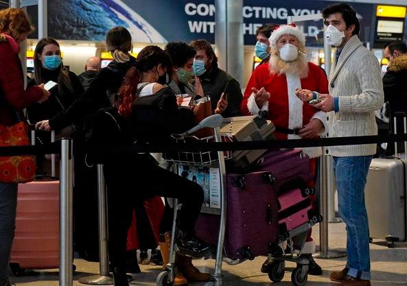 Los viajeros hacen cola con su equipaje en una sala de salidas de Heathrow el lunes, ya que países como Canadda prohibieron a los viajeros del Reino Unido debido a una nueva cepa de COVID-19.