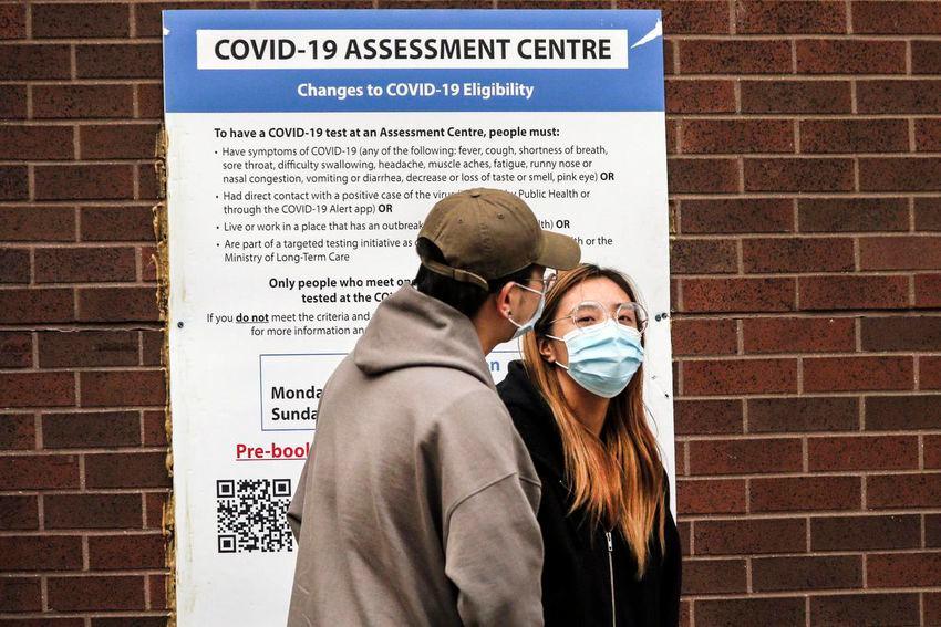 Una pareja espera fuera del centro de evaluación Covid-19 del Toronto Western Hospital en Bathurst Street.
