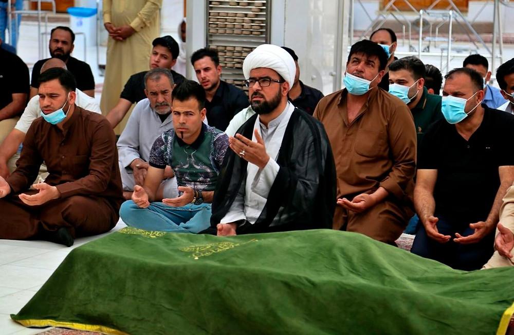 Los dolientes rezan cerca del ataúd de un paciente con coronavirus que murió en el incendio de un hospital, durante su funeral en el Santuario Imam Ali en Najaf, Irak, el domingo 25 de abril de 2021.