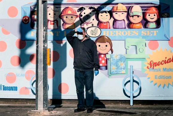 Un hombre que lleva una máscara se protege los ojos del sol antes de cruzar la calle en Toronto esta semana.