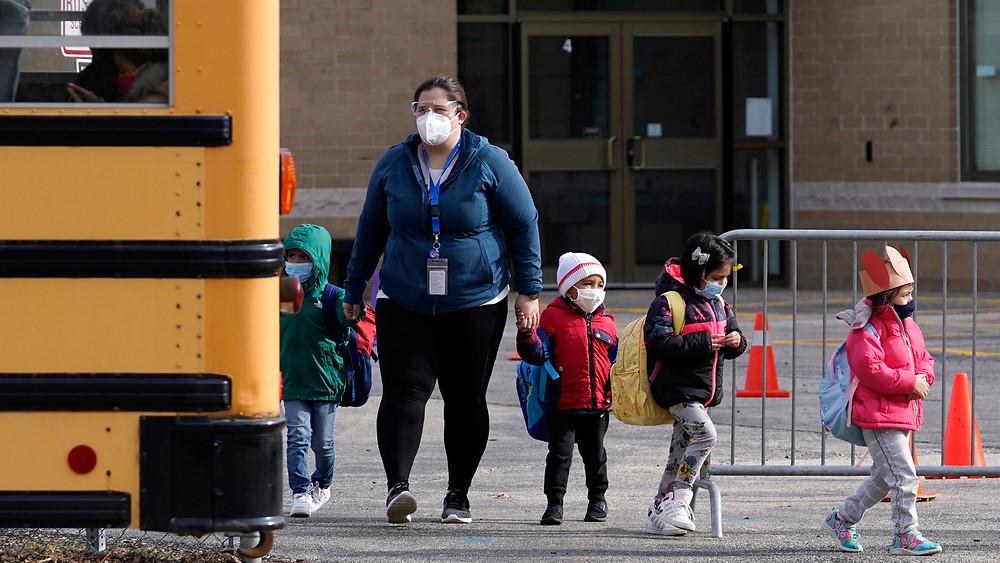 estudiantes caminan hacia un autobús escolar con un maestro después de asistir a la escuela