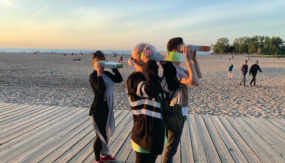 Observadores del cielo utilizan cajas de cereales modificadas para ver el eclipse solar en Woodbine Beach en Toronto el 10 de junio de 2021.