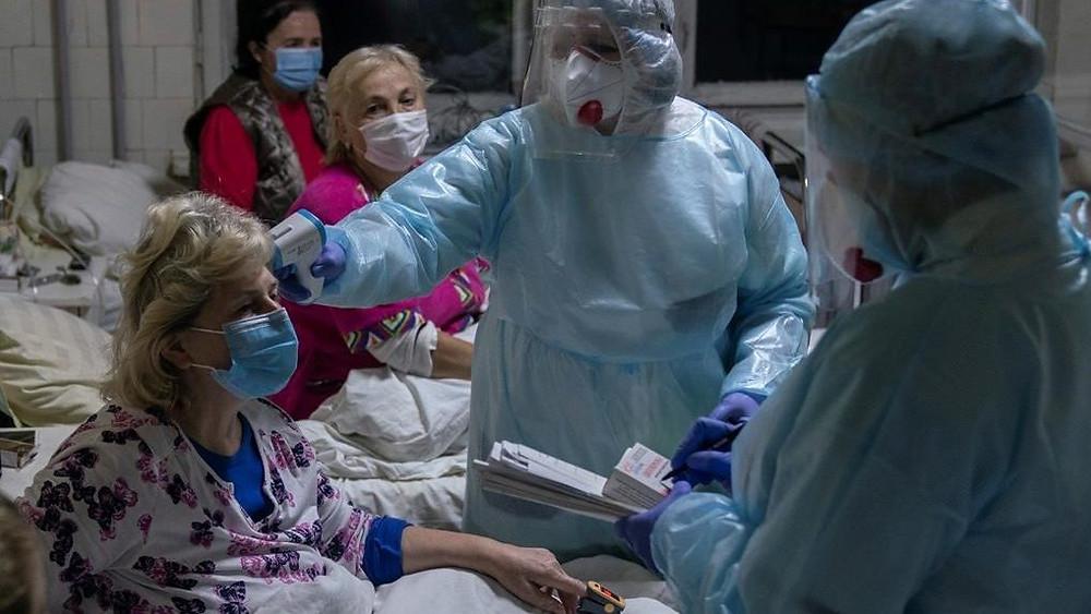 enfermera revisa la temperatura de un paciente con coronavirus en Stebnyk, en el oeste de Ucrania