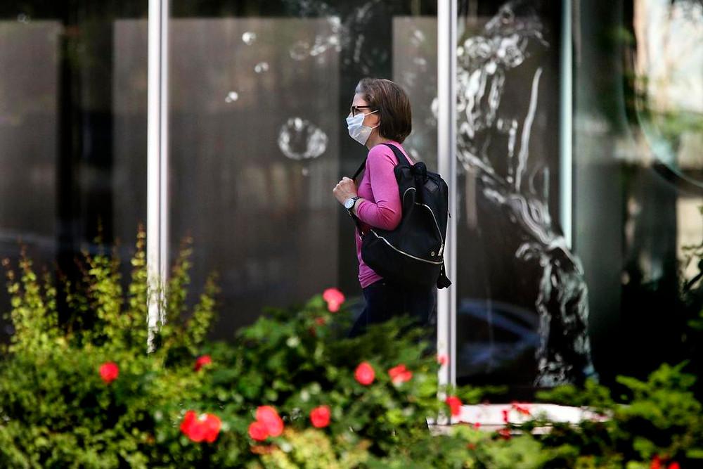 Una mujer con una mascarilla camina en el centro de Toronto