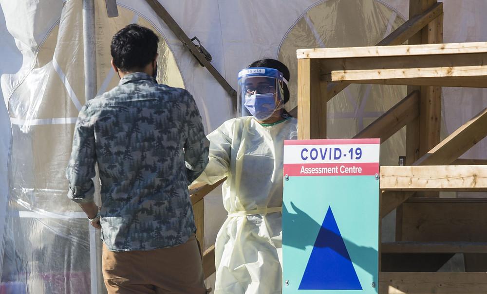 Una trabajadora médica con equipo de protección habla con un hombre fuera de un centro de evaluación de COVID-19 en Toronto, Canadá, el 8 de noviembre de 2020.