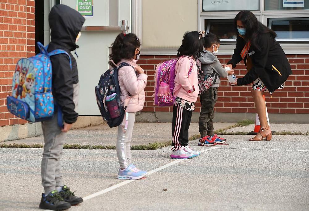 Los niños de kindergarten reciben desinfectante antes del comienzo de clases el martes.