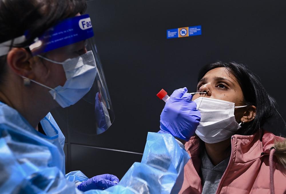 Khushpreet Gulati, a la derecha, llega de India y recibe una prueba obligatoria de COVID-19 en el Aeropuerto Internacional Pearson durante la pandemia de COVID-19 en Toronto el lunes 1 de febrero de 2021.