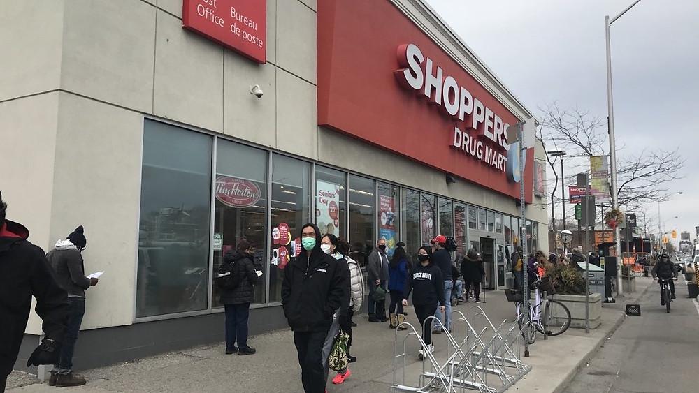 Personas entre 60 y 64 años esperan en la fila de un Shoppers Drug Mart de Toronto para recibir su vacuna COVID-19 de AstraZeneca.