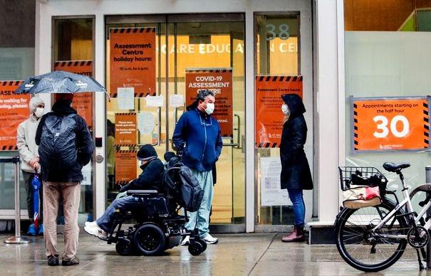 La gente espera bajo la lluvia fuera del centro de evaluación COVID-19 del Hospital St. Michael's en Toronto.
