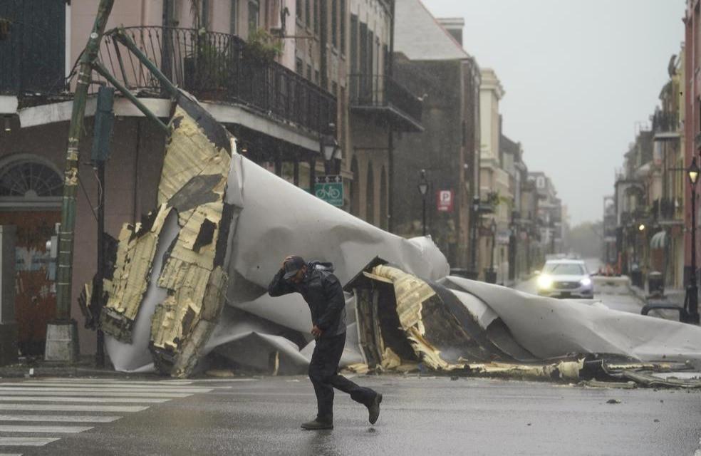 Un hombre pasa por una sección del techo que se desprendió de un edificio en el Barrio Francés por los vientos del huracán Ida, el domingo 29 de agosto de 2021, en Nueva Orleans.