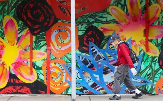 Un paseo colorido durante una temporada lúgubre. Un peatón sube por Church Street cerca de Dundas pasando el mural, Street Flowers del artista Daniel Mazzone, sobre el acaparamiento de un proyecto de construcción.