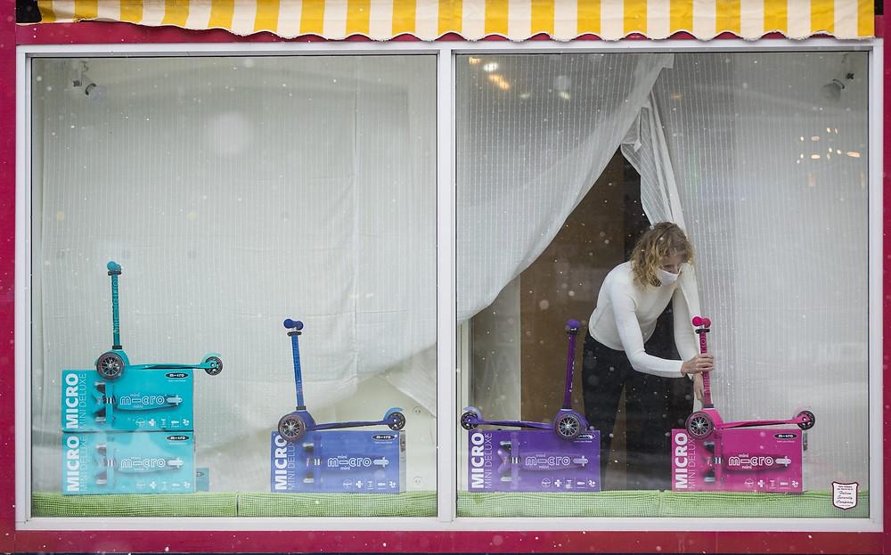 Una persona usa una mascarilla decora el escaparate de una tienda en Kingston, Ontario, el viernes 19 de febrero de 2021.