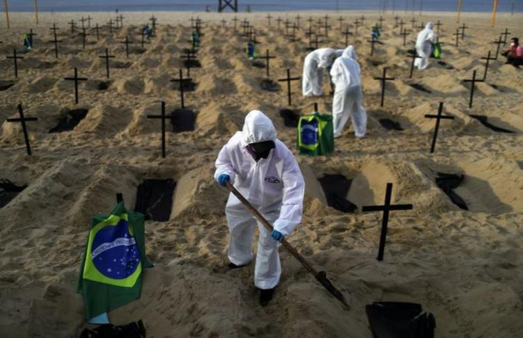 Activistas de la ONG Río de Paz con equipo de protección cavan tumbas en la playa de Copacabana para simbolizar a los muertos por la enfermedad del coronavirus durante una manifestación en Río de Janeiro, Brasil, el 11 de junio de 2020.