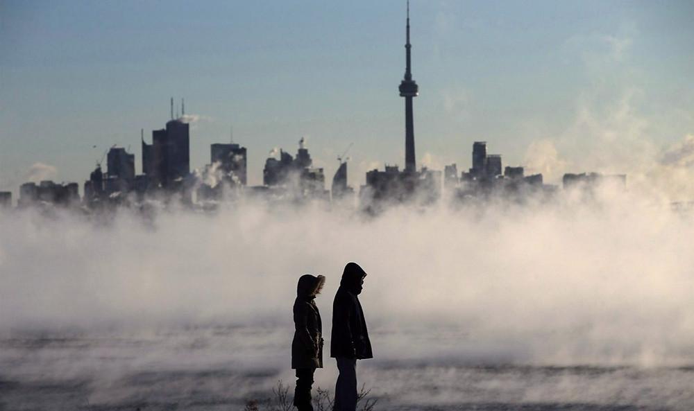 El vapor sube mientras la gente mira hacia el lago Ontario frente al horizonte durante el frío extremo en Toronto el 13 de febrero de 2016.