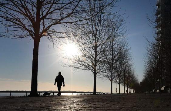 Un peatón camina a lo largo de la orilla del lago al pie de Sherbourne St. el 8 de enero de 2021 mientras el sol cuelga bajo en el cielo. La pandemia de COVID-19 se está recuperando y continúa imponiendo aislamiento y distanciamiento en Toronto y en todo el mundo.