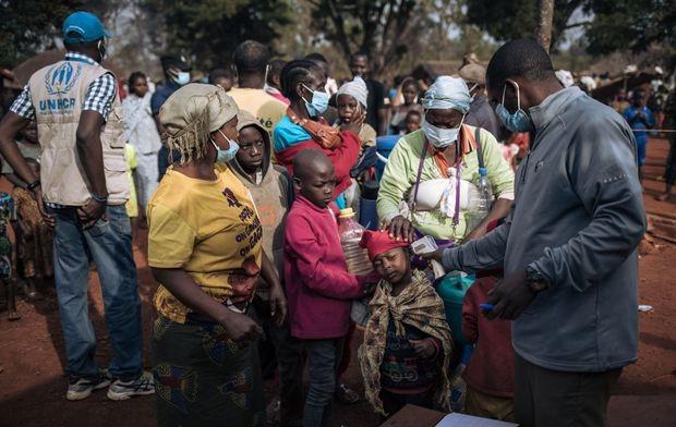 Agentes del Alto Comisionado de las Naciones Unidas para los Refugiados (ACNUR) realizan un control de temperatura como parte de las medidas COVID-19 en la entrada de un sitio de registro de refugiados en Ndu, provincia de Bas-Uele, República Democrática del Congo el 21 de enero de 2021.