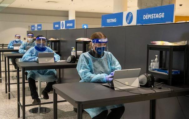 Los trabajadores se preparan para recibir a los pasajeros en el centro de pruebas COVID-19 en el área de llegadas internacionales del aeropuerto Pearson de Toronto el 26 de enero de 2021.
