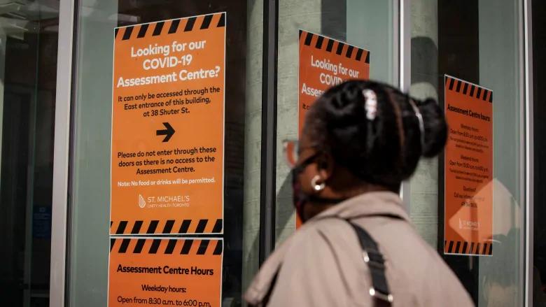 mujer entra a un centro de evaluación de COVID-19 en el Hospital St. Michael's en el centro de Toronto.