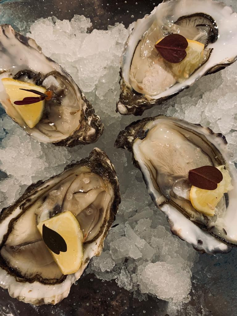 oysters on ice with lemon and butterfly sorrel