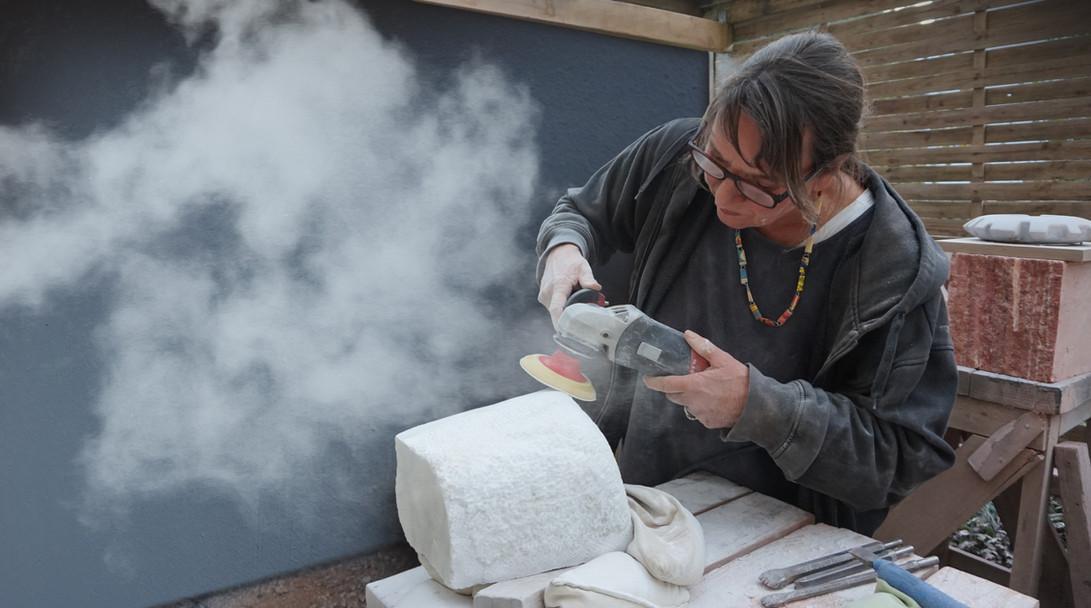 Ulla Preising bei der Arbeit an einer Skulptur mit der Flex. Hier wird der Stein geschliffen.