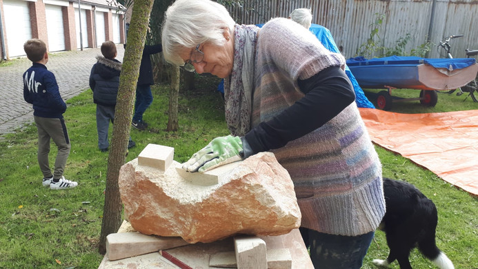 Sie auch. Kursteilnehmerin bearbeitet ihre Skulptur mit Hammer und Meissel.