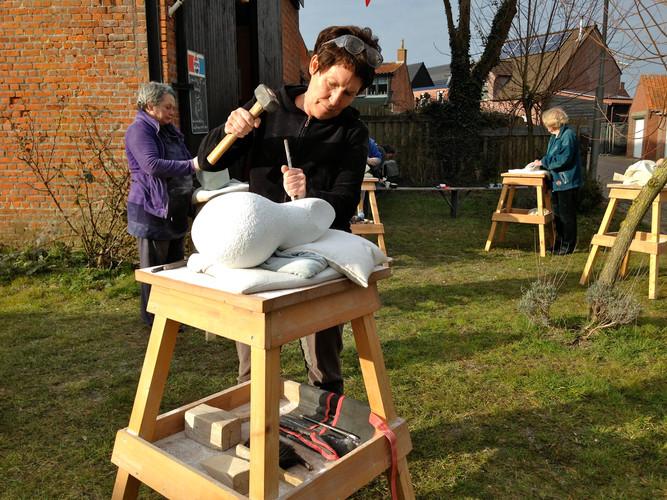 Bildhauern mit Hammer und Meissel. Doe Teilnehmerin ist konzentriert bei der Arbeit.