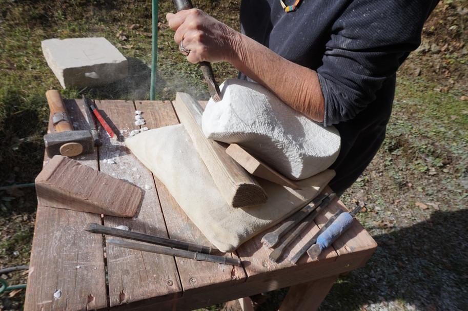 Bei der Arbeit am einer Skulptur mit Bildhauerwerkzeugen für die Handarbeit.