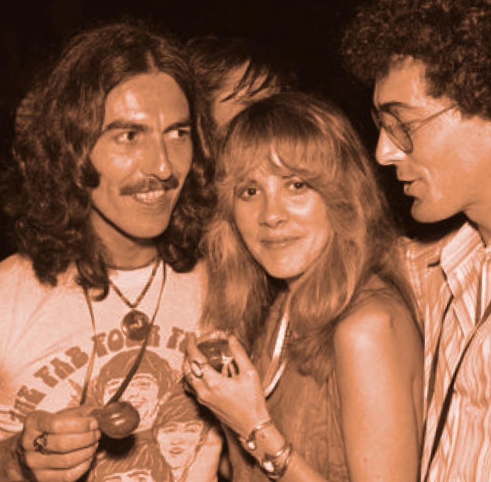 George Harrison portant le T. Shirt du Club des 4 de Liverpool - The Fab Four Fun Club (dessiné par l'artiste Jean Solé) posant avec Stevie Nicks de Fleetwood Mac en 1974.
