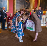Olivia, a service user from The Teapot Trust, presents Her Royal Highness with a tea towel she designed during her in-hospital art classes