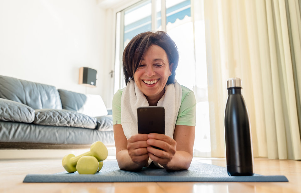 Middle Age Woman Exercising at Home on her Phone through Mavericks Fitness App