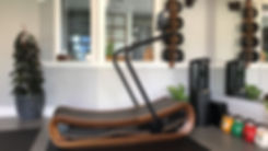 Curved Incline Manual Treadmill Made out of Walnut in Personal Training Gym