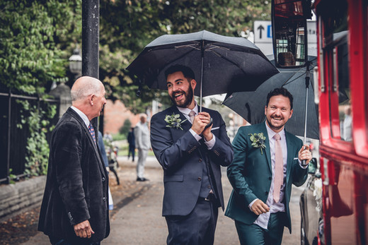 Grooms boarding a London Bus in the Rain