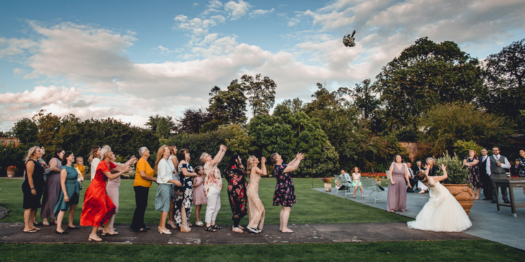 Original photo of bride throwing bouquet at Irnham Hall Wedding