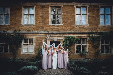 Bride and bridesmaids pose for a fun photo at Allington Manor