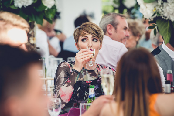 Wedding guest drinking champagne at wedding reception, Irnham Hall