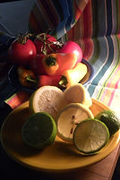 Still life photograph of lemons, limes, peppers and tomato